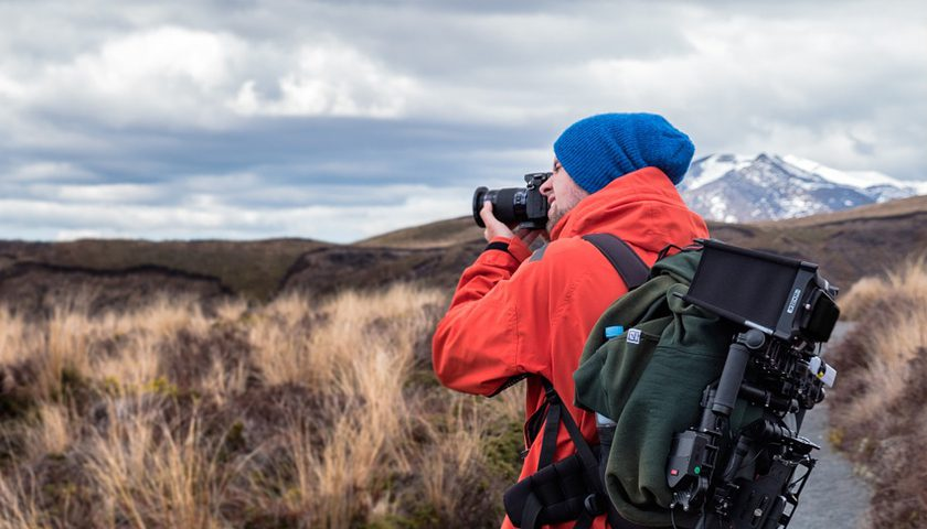 Seyahat zoom lensi kullanan bir doğa fotoğrafçısı